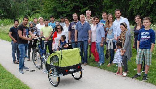 Übergabe von Fahrradanhängern an junge Flüchtlingsfamilien
