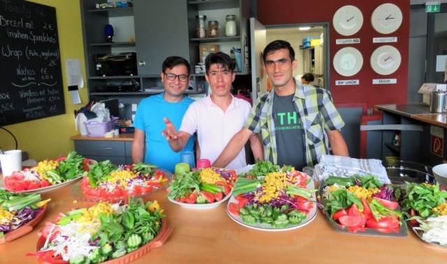 Ekrem, Milad und ein weiterer Freund arrangieren die Salate auf der Theke